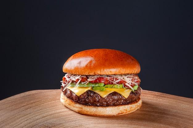 Köstlicher rindfleischburger mit tomatensauce, parmesankäse und salat auf holztisch auf dunklem hintergrund. platz kopieren