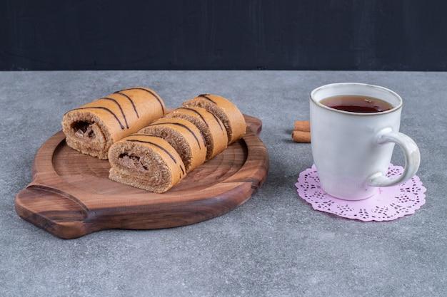Köstlicher rollkuchen auf holzplatte mit tasse tee
