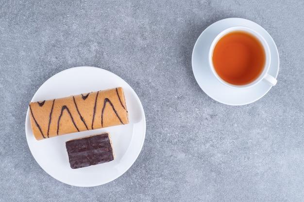 Köstlicher rollkuchen mit schokolade auf weißem teller und tasse tee