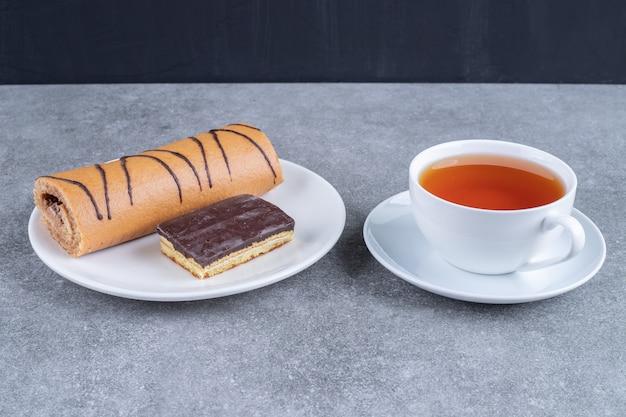 Köstlicher rollkuchen mit schokoladenkuchen auf weißem teller und tasse tee