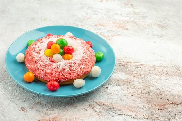 Köstlicher rosa kuchen der vorderansicht mit bunten bonbons innerhalb des tellers auf weißer bodentorte regenbogenfarbenkuchen-dessertsüßigkeit