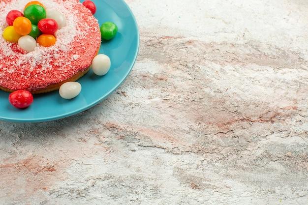 Köstlicher rosa kuchen der vorderansicht mit bunten bonbons innerhalb des tellers auf weißer schreibtischtorte regenbogenfarbenkuchen-dessertsüßigkeit