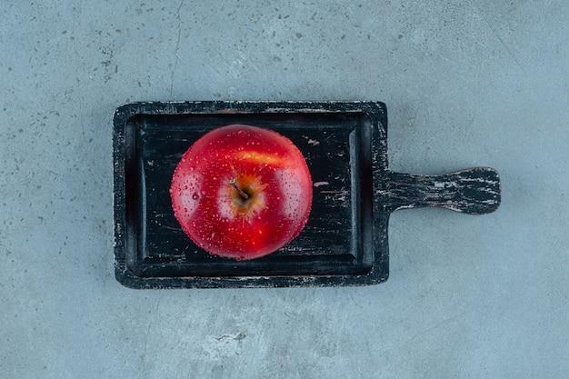 Köstlicher roter apfel auf einem brett, auf dem marmorhintergrund. foto in hoher qualität