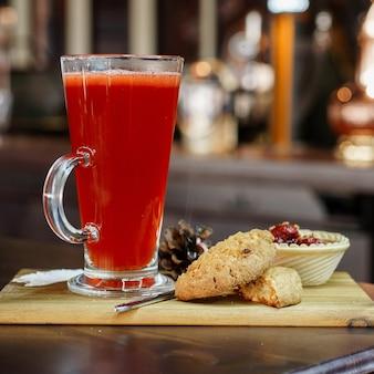 Köstlicher roter cocktail mit einem süßen dessert von erdbeeren und keksen auf einem holzbrett in einem restaurant