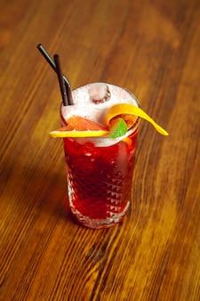 Köstlicher roter cocktail mit orangen- und limettenscheiben auf dem tisch