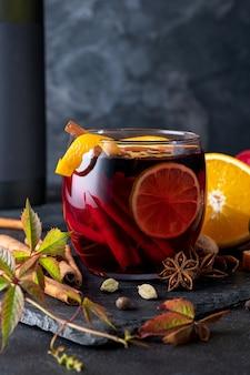 Köstlicher rotwein mit gewürzen. glühwein und zutaten auf dunklem tisch