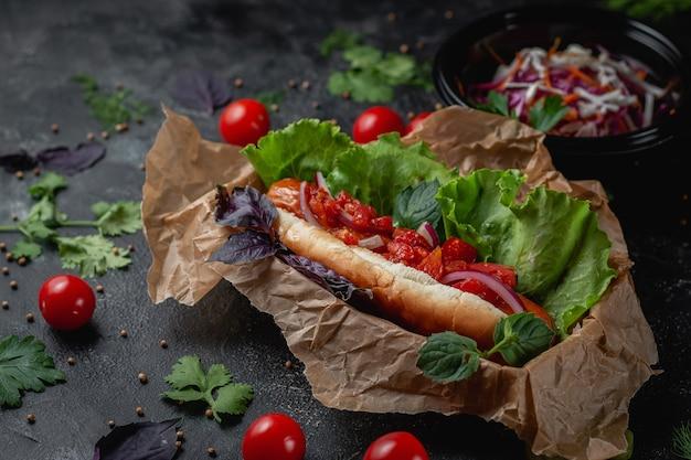Köstlicher saftiger hot dog mit käsesauce, tomaten und frischen kräutern im sortiment, sandwich auf der speisekarte eines fast-food-restaurants auf einem dunklen steintisch. gesunde alternative zu fast food.