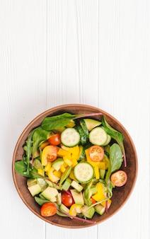 Köstlicher salat auf einer schüssel über dem weißen hölzernen schreibtisch