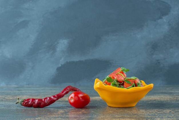 Köstlicher salat im gelben teller mit pfeffer und tomate auf marmorhintergrund