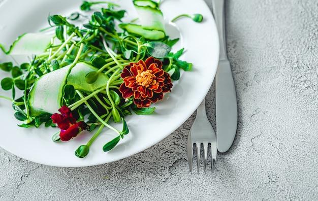 Köstlicher salat mit blumen, gabel und messer