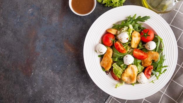 Köstlicher salat mit hühnchen, mozzarella, rucola und kirschtomaten. ansicht von oben, textfreiraum