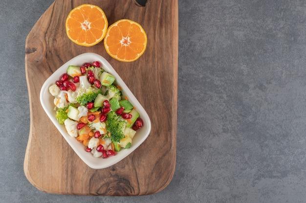 Köstlicher salat und frische mandarine auf marmorhintergrund. foto in hoher qualität