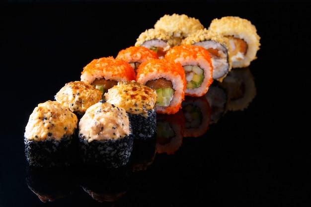 Köstlicher satz sushirolle mit fischen auf einem schwarzen hintergrund mit reflexion menü und restaurant