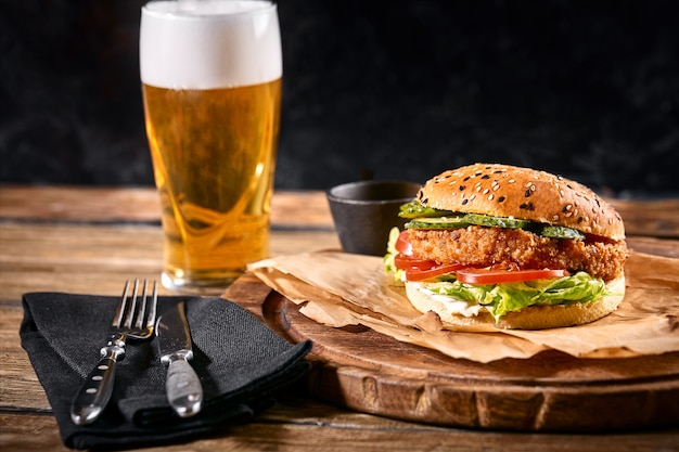 Köstlicher scharfer schwarzer burger mit chili-pfeffer und einem glas bier