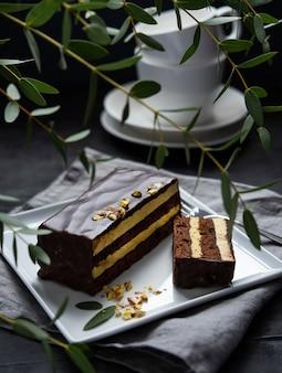 Köstlicher schokoladen-mozart-kuchen mit pistazien auf dunklem hintergrund des quadratischen plattenmorgenlichtfensters