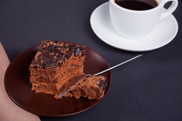 Köstlicher schokoladenkuchen auf der braunen platte mit tasse kaffee auf der schwarzen tabelle