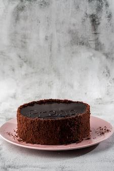 Köstlicher schokoladenkuchen auf teller auf tisch auf marmorhintergrund. tapete für konditorei oder cafémenü. vertikale.