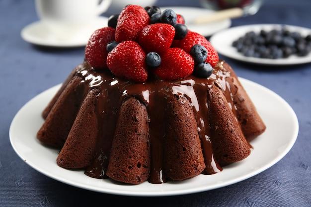 Köstlicher schokoladenkuchen mit erdbeeren im teller auf tisch, nahaufnahme