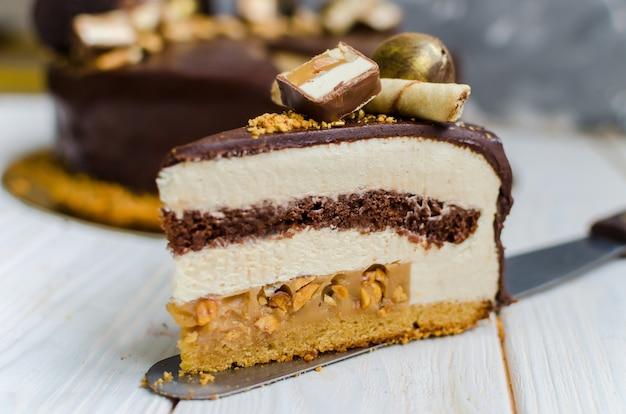 Köstlicher schokoladenkuchen mit keks, mousse-schichten, süßigkeiten und erdnüssen.