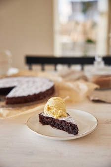 Köstlicher schokoladenkuchen mit sahne auf einem weißen tisch mit ästhetischen details präsentiert