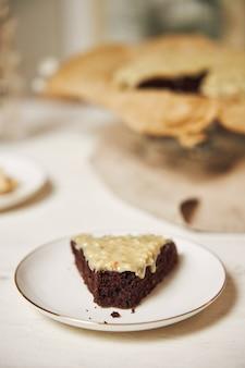 Köstlicher schokoladenkuchen mit sahne auf einem weißen tisch präsentiert