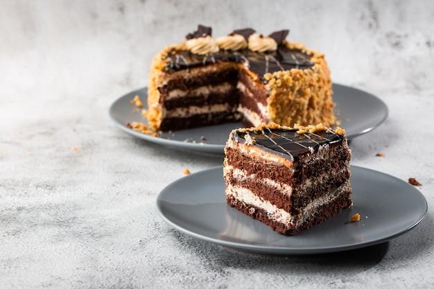 Köstlicher schokoladenkuchen mit weißer kokoscreme auf teller auf tisch auf marmorhintergrund. tapete für konditorei oder cafémenü. horizontal