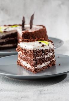 Köstlicher schokoladenkuchen mit weißer kokoscreme auf teller auf tisch auf marmorhintergrund. tapete für konditorei oder cafémenü. vertikale.