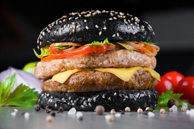 Köstlicher schwarzer saftiger burger mit frischen tomaten, paprika und kräutern