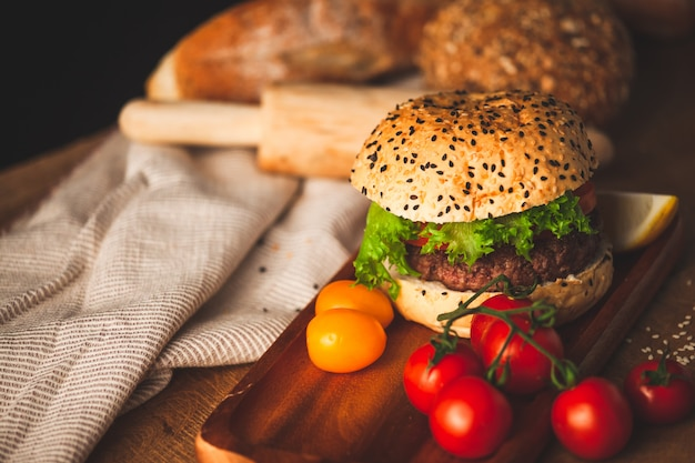 Köstlicher selbst gemachter hamburger mit frischgemüse in der küche servierfertig und isst