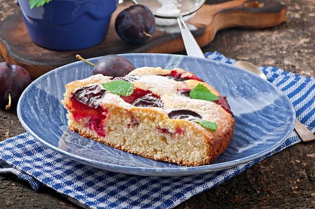 Köstlicher selbst gemachter kuchen mit pflaumen auf einer holzoberfläche