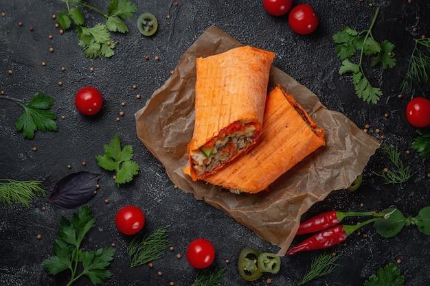 Köstlicher shawarma und tacos in einem käselavash auf einem dunklen steintisch. fastfood-restaurant. gesunde alternative zu fast food. leckere frische wrap-sandwiches mit rindfleisch und gemüse, traditional middle