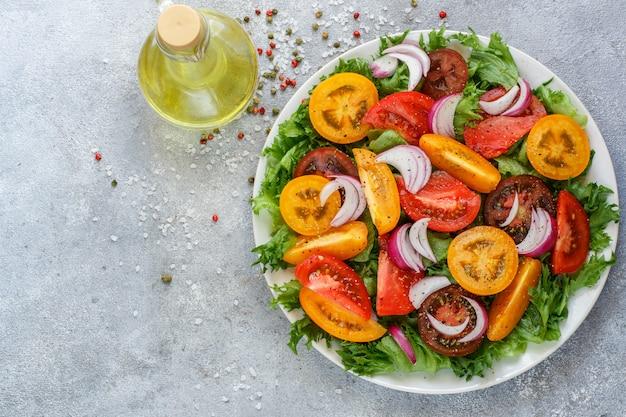 Köstlicher sommersalat aus bunten tomaten, roten zwiebeln und salat mit gewürzen