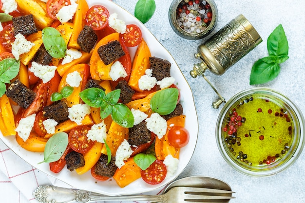 Köstlicher sommersalat aus gelben und roten tomaten, croutons, käsemozzarella, basilikum und olivenöl