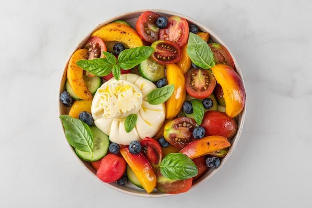 Köstlicher sommersalat mit burrata-käse, gegrillten pfirsichen, tomaten, blaubeeren, gurken, olivenöl und basilikum. ansicht von oben. gesunde ernährung