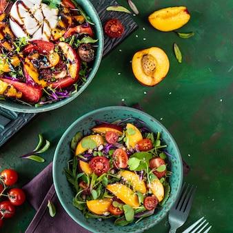 Köstlicher sommersalat mit burrata-käse und gegrillten pfirsichen, rucola und microgreens. gesundes essen. flach liegen.