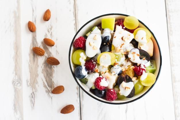 Köstlicher sommersalat mit frischen früchten und beeren, mandeln in einer schüssel auf weißem holzhintergrund.