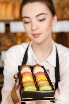 Köstlicher tagesstart. nahaufnahmeporträt eines schönen weiblichen bäckers, der obsttörtchenkuchen zur vitrine setzt
