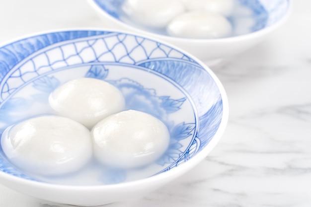 Köstlicher tang yuan, yuanxiao in einer kleinen schüssel. asiatische traditionelle festliche speisen reisknödel ball mit gefüllten füllungen für das chinesische laternenfest, nahaufnahme.