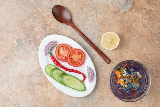 Köstlicher tee mit gurke, tomate, zitronenscheibe und löffel auf weißem teller