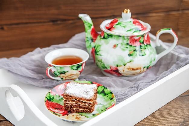 Köstlicher tee und scheibe des kuchens auf einem hölzernen behälter.