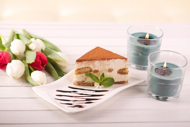 Köstlicher tiramisukuchen und tulpenblumen als geschenk