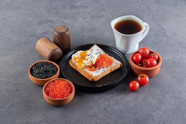 Köstlicher toast mit roten frischen kirschtomaten und einer tasse tee.