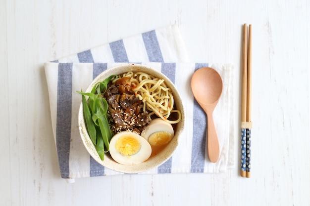 Köstlicher udon mit ei und rindfleisch auf der schüssel mit löffel und essstäbchen