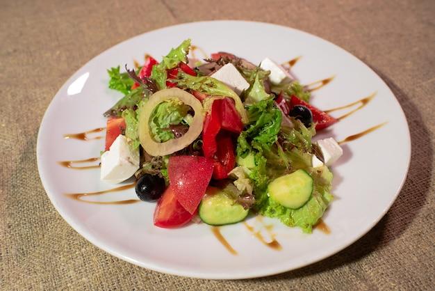 Köstlicher und gesunder griechischer salat auf einem weißen teller