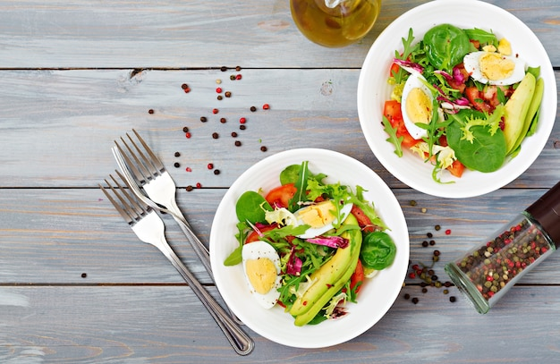 Köstlicher und leichter salat aus tomaten, eiern und einer mischung aus salatblättern. gesundes frühstück. ansicht von oben