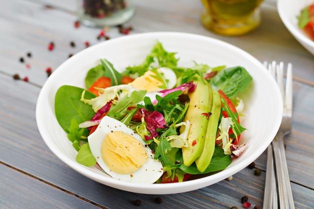 Köstlicher und leichter salat aus tomaten, eiern und einer mischung aus salatblättern. gesundes frühstück.