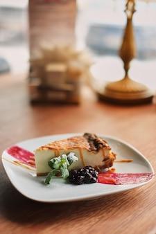 Köstlicher und süßer blaubeerkäsekuchen auf weißer platte diente mit schlagsahne