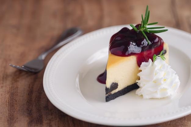 Köstlicher und süßer heidelbeer-new- yorkkäsekuchen auf der weißen platte gedient