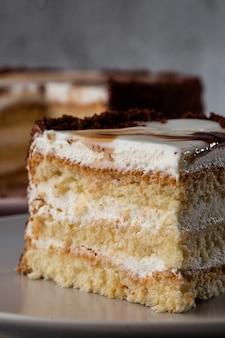 Köstlicher victoria-biskuitkuchen mit weißer sahne auf teller auf tisch auf marmorhintergrund. tapete für konditorei oder cafémenü. vertikale.