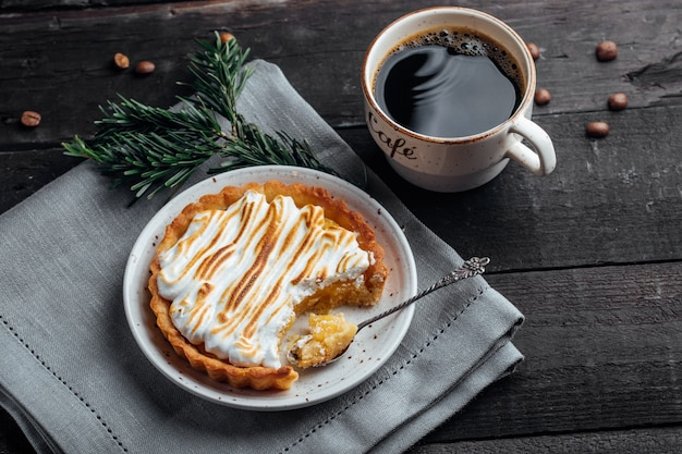 Köstlicher weihnachtsdessert. zitronentörtchen mit meringe und tasse kaffee auf dunklem holztisch. weihnachtsferien dekoration